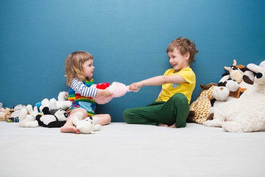 Two little kids, brother and sister fighting over a toy. the conflict between children..