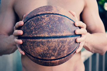 Man holding basketball shirtless with rough grunge ball for sport.
