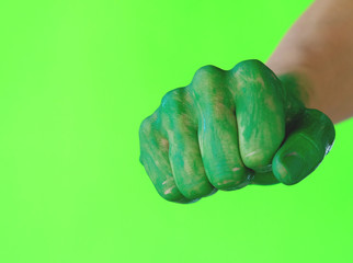 Green human hand in fist for strong punch gesture. Concept of power and strength.
