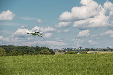 Little plane approaching and the green german countryside
