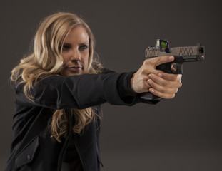 Blonde female shooter aiming gun.