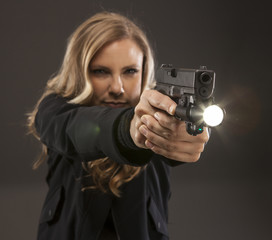 Woman pointing a gun with a light.