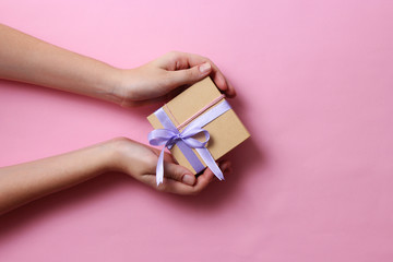 gift in female hands on a colored background. Holiday, minimalism, congratulations.