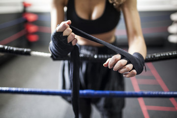 Fitness woman in sport clothes coiling boxing bandage