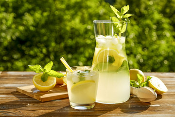 Iced lemonade pitcher, juicer and one glass of cold citrus beverage with lemon slices, mint leaves & yellow straws on brown grunged wooden table, country side foliage background. Close up, copy space.