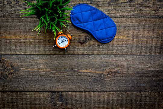 Healthy sleep concept. Sleeping mask near alarm clock on dark wooden background top view copy space