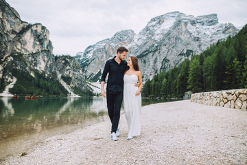 Young couple walk near a beautiful lake that is in the mountains of the italy. the women are dressed in beautiful clothes the girl is dressed in a white dress