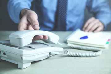Businessman calling in office telephone. Contact concept