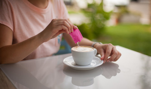Woman hand pouring a sugar packet into a cup of coffee.