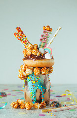 Chocolate freak shake with donut on party table with copy space