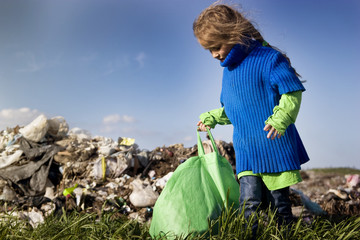 Poor hungry child tries to lift a heavy bag in a garbage dump on a blue sky background