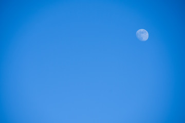 Bright little full blue moon against a blue sky in the afternoon, background, copyspace