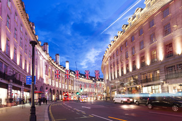 Foto auf Leinwand London roten bus Popular tourist Regent street with flags union jack in night lights illumination in London, England, United Kingdom