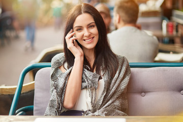Beautiful happy brunette female with gentle smile, speaks via smart phone with friend, shares latest news, poses in outdoor cafe, looks positively at camera. People and communication concept