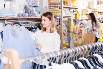 Smiling woman choosing blue sweater in the modern shop