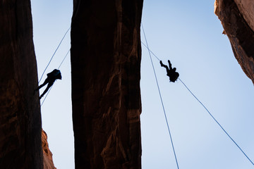 People rappelling off of Morning Glory Arch in Moab, Utah.