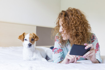 young beautiful woman lying on bed with her cute small dog, taking a selfie with mobile phone and smiling. Home, indoors and lifestyle. Daytime