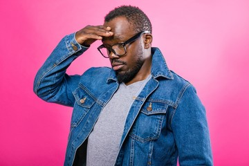 Thoughtful African man with glasses standing on a pink background brought his hand to his head
