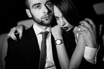 Girl and Guy in the car.Girl and Guy in the backseat.The guy in the suit girl in a white dress and jacket.Passion and love in the car.Couple of lovers.Black and white