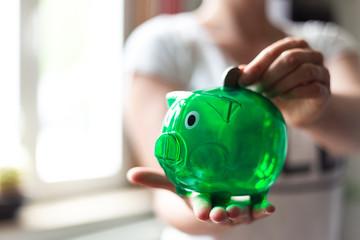 Aktives sparen. Frau wirft Geld in ein grünes Sparschwein