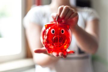 Geld in ein rotes Sparschwein werfen
