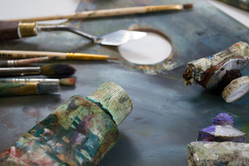 Bright oil paints in a tube on a dirty palette. Paints in use.