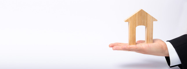 The businessman's hand stretches a wooden house with a large doorway. The concept of commercial real estate, the purchase and sale of residential buildings, apartments. Rental of property. Banner
