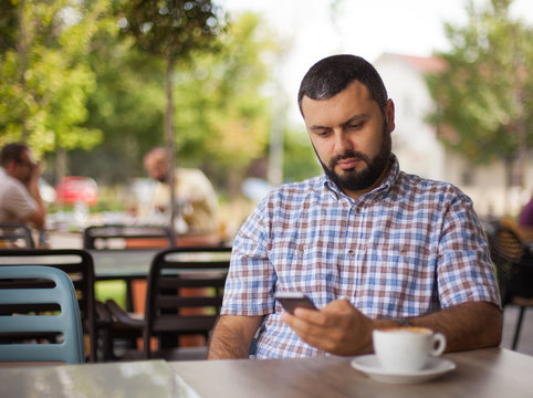 Handsome man using phone in cafe.