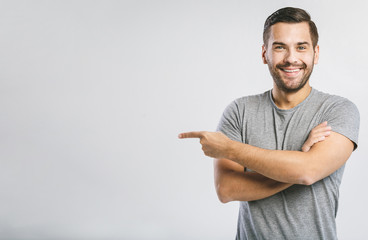 Look over there! Happy young handsome man in jeans shirt pointing away and smiling while standing against white background