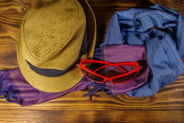 Red sunglasses, straw hat and summer scarf on wooden background