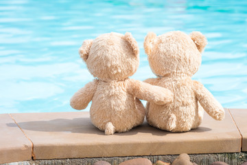 Two teddy bears pool edge view. Love and relationship concept.