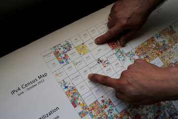 Workers of a data center point to the Apple and IBM companies on a picture showing a IPv4 census map of the year 2012, at DataRush IT Services company in Malaga