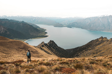 New Zealand, Isthmus peak: young man with Magnificent view of beautiful lake in rocky mountains