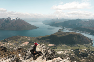 New Zealand: young man with Magnificent view of beautiful lake in rocky mountains