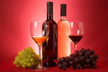 Red and white wine bottles; grape an drinking glasses