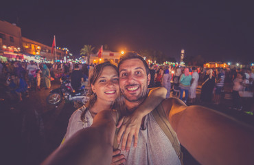 Happy tourists take selfie photo in the most important main square of Morocco Unesco site.  Jamaa el-Fna market Marrakech at evening. Wall mural