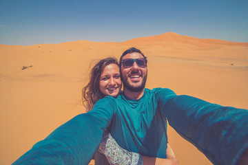 Happy tourist couple smiling take photo selfie in the Middle of the red Sahara desert with giant red dunes in background