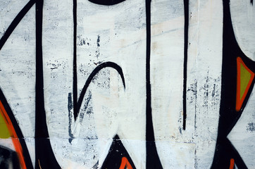 Street art. Abstract background image of a fragment of a colored graffiti painting in white and orange tones