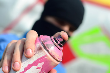 A young graffiti artist in a blue jacket and black mask is holding a can of paint in front of him against a background of colored graffiti drawing. Street art and vandalism concept
