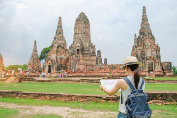 Young Woman traveling backpack with map, Asian traveler looking to Wat Chaiwatthanaram temple in Ayutthaya Historical Park, a UNESCO world heritage site in Thailand. summer Travel concept