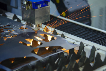 The CNC laser cutting machine cutting the metal plate with the sparking light.Hi-technology sheet metal process.
