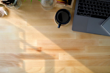Laptop with brown coffee cup and copy space on the wooden desk table. workspace and copy space.