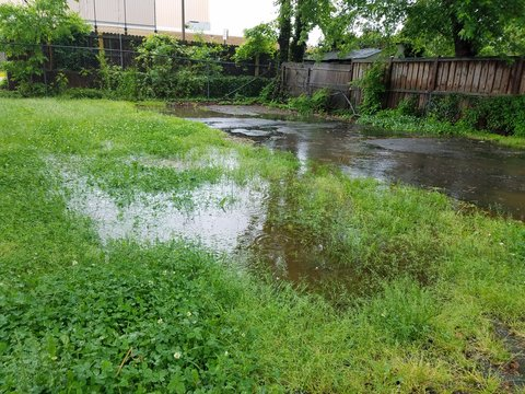 large water puddle from rain in driveway and grass