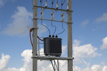 Electric transformer stands on concrete supports.