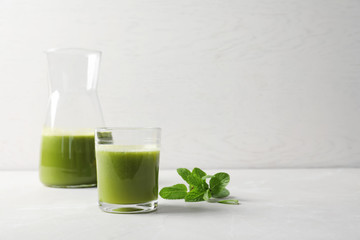 Glassware with delicious detox juice and mint on table