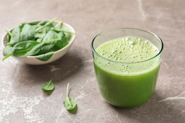 Glass with delicious detox juice and spinach on table