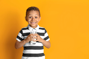 Adorable African-American boy with glass of milk on color background