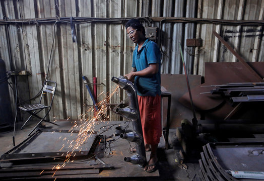 A worker grinds a steel pipe to be used in air ducts inside a workshop at an industrial area in Mumbai