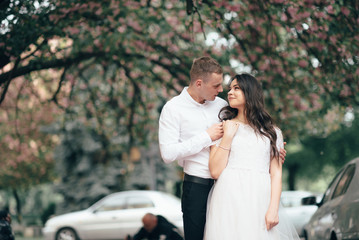 Happy young couple in love enjoys spring day, loving man holding on hands his woman carefree walking at park
