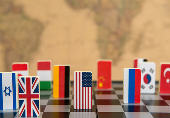 symbols of countries on the chessboard against against the background the political map of the world. Conceptual photo, political games.
